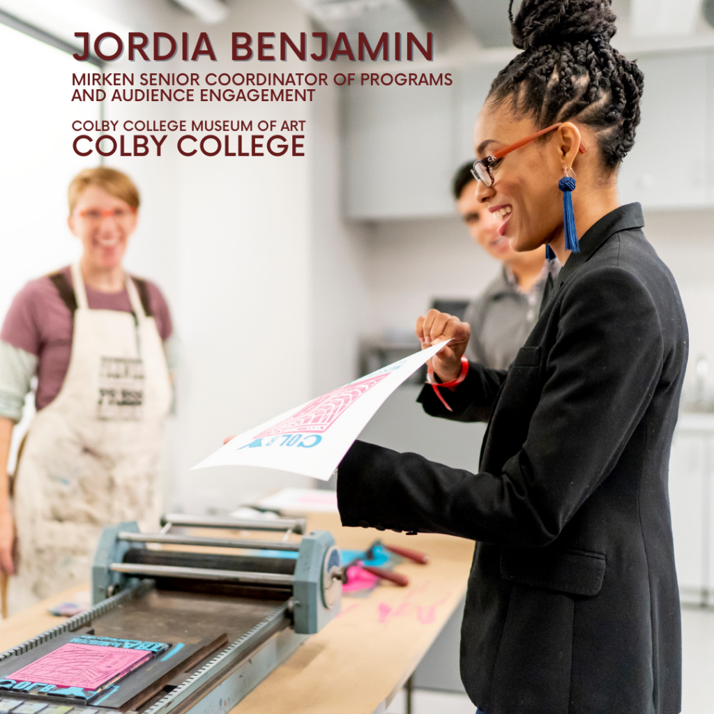 Member of the Month for June 2021, Jordia Benjamin is holding a print fresh off a printing press.