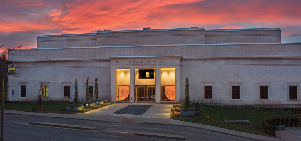 Image of the front of the Spencer Museum of Art taken at sunset so the background is filled with pink, red, orange, and deep violet hues.